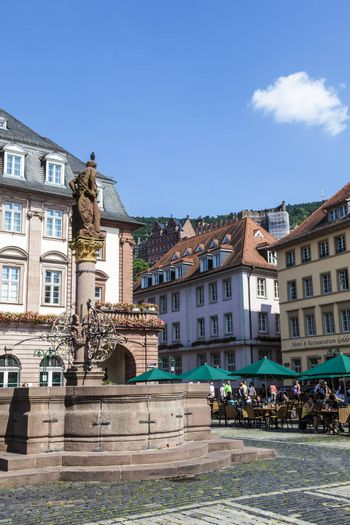 HEIDELBERG, GERMANY - JULY 7, 2013: people visit Herkules fountain Heidelberg, Germany. The fountain at the central market place was build in 1709.