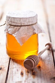 full honey pot and honey stick
