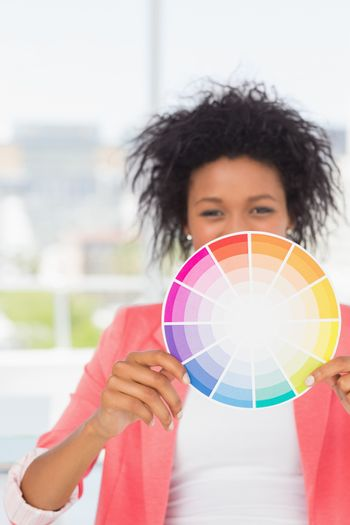 Portrait of a beautiful young woman holding color wheel at bright office