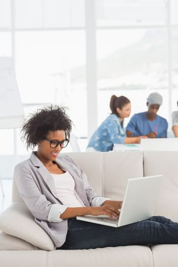 Young woman using laptop with colleagues in background at a creative bright office