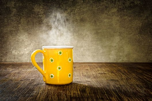 Colorful steaming coffee mug on the table