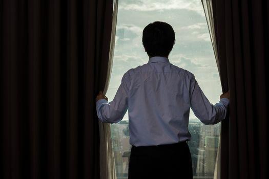 businessman draw the curtain