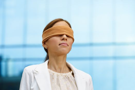 Blindfolded hispanic business woman near office building