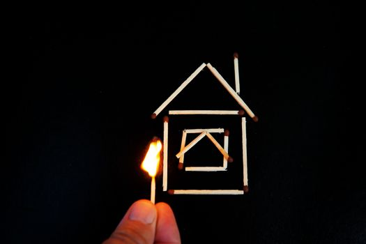 burning match in hand near the model of the house