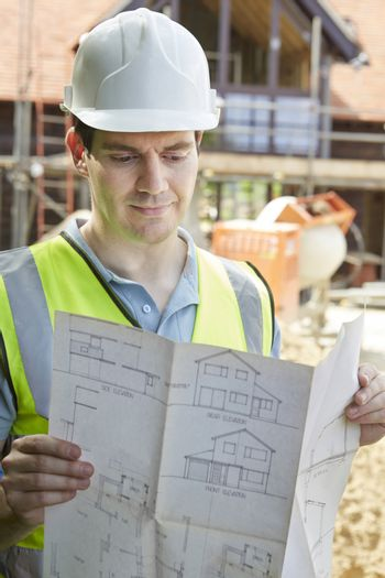Construction Worker On Building Site Looking At House Plans