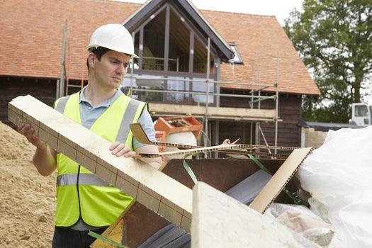 Builder Putting Waste Into Rubbish Skip