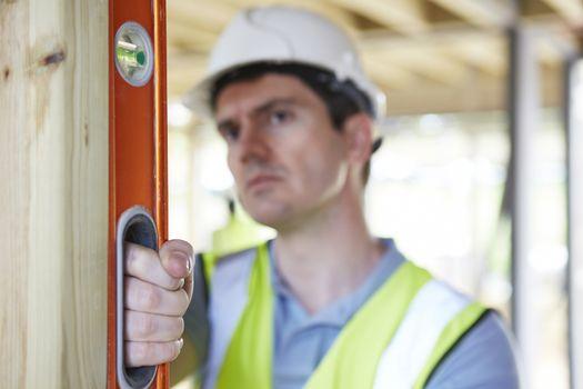 Builder Checking Work With Spirit Level