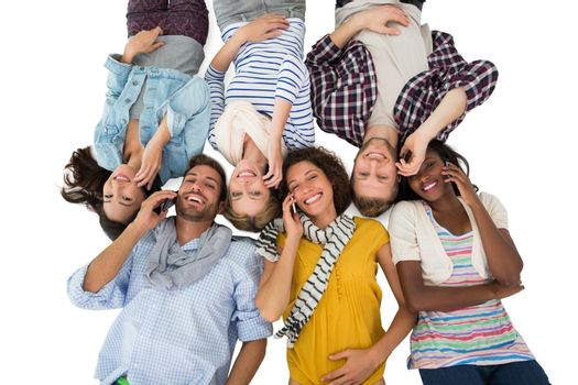 Happy group of friends lying on the floor on their phones on white background