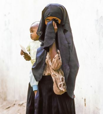 HADHRAMAUT, YEMEN - MAY, 15: arabic unknown mother carries her baby in a  wraparound garment on May 15, 1993 in Hadhramaut, Yemen. in 2008 still 62 percent of women in rural areas are  illiteracy.