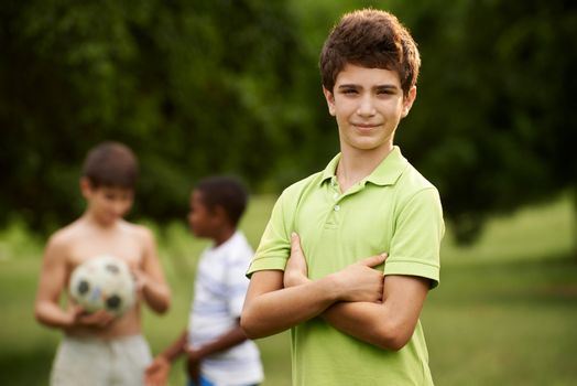 Portrait of elementary age kid looking at camera with arms crossed and children playing soccer in background