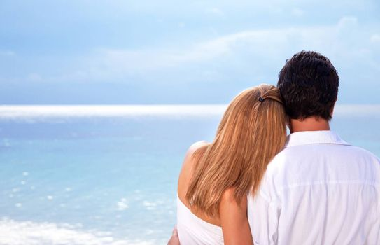 Rear view of young couple hugging on the beach, honeymoon on Maldives, enjoying wonderful seaview, love concept