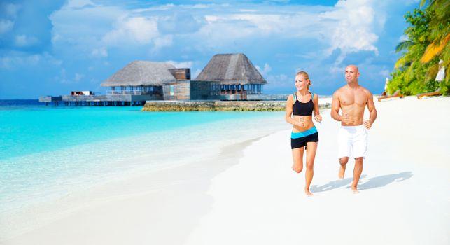 Happy couple jogging on the beach