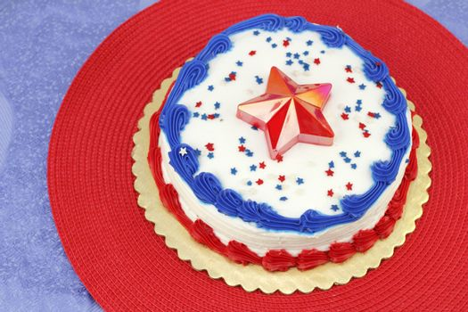 Round Independence Day holiday cake decorated with white frosting, red and blue ribbons, edible stars and a red plastic star on the center top. The cake is on a gold base, then red and blue placemats.