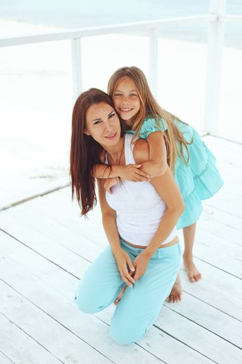 Mother with her 7 years old daughter having fun at beach in summer