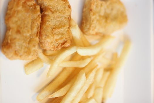 French fries and fried chicken on dish in the restaurant.