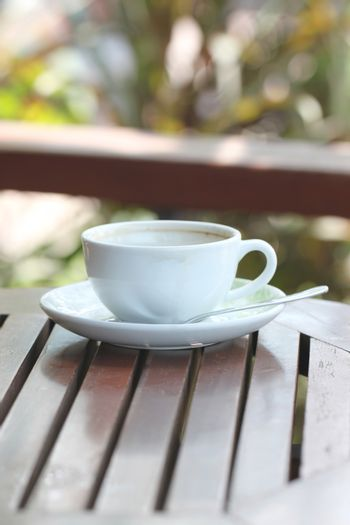 White coffee cup on brown wood table.