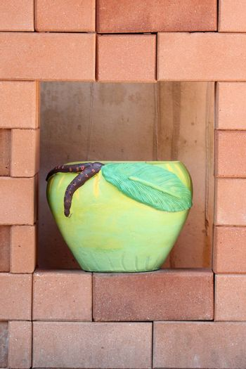 jardiniere on brown brick wall for interior background.