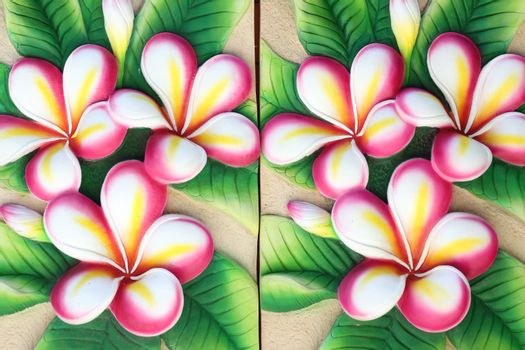 Artificial plumeria on brown wall for house interior.