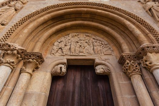 Arhivolts, capitals and carved tympanum  detail view of the romanesque style door  called Puerta del Cordero in the Royal San Isidoro collegiate church from the X century i n Leon Spain