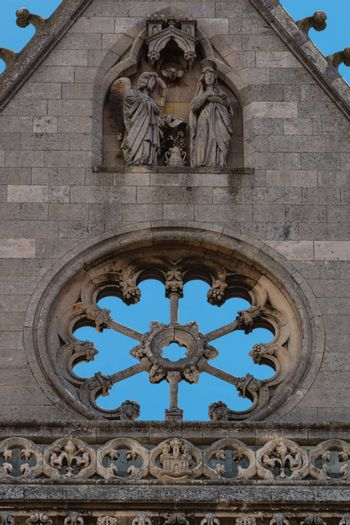 Detail of carved religious scene and stoned rose window inthe main facade of the gothic cathedral in Leon,Spain