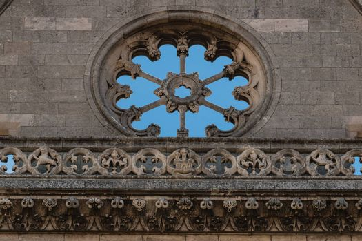 Stoned rose window and balustrade in main facade of gothic leon Cathedral in spain