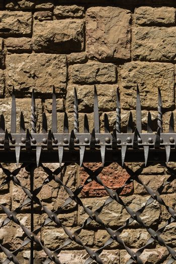 Fine protective barrier with forged prongs and a solid stoned wall in the background in the city center of Leon , Spain