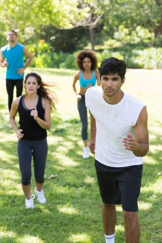 Athletes jogging on grassy land