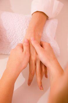 Masseuse massaging hand