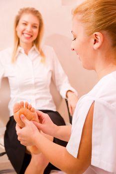 Therapist's hands massaging female foot