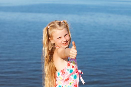 happy girl showing sign okay with fingers on seashore