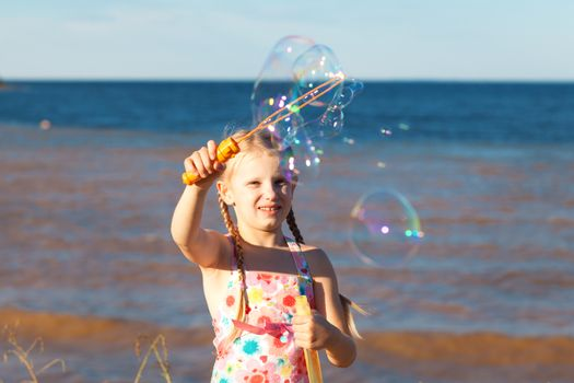 gilrl with soap bubbles on the seashore