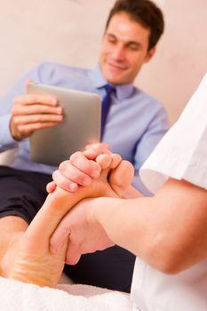 Masseuse massaging businessman's foot