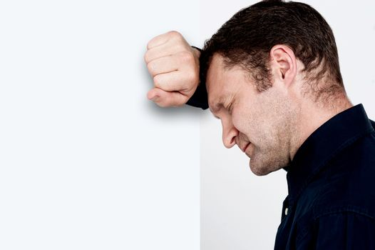 Unhappy man leaning at the wall