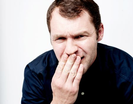 Handsome man covering his mouth with hand