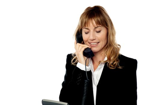Smiling female executive attending phone call