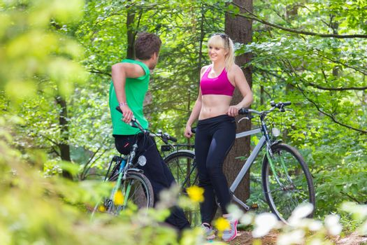 Young spoty active cople biking in nature. Active lifestyle. Activities and recreation outdoors.
