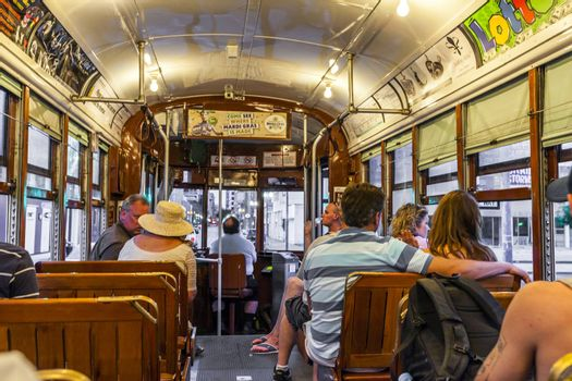 NEW ORLEANS - JULY 14, 2013: people travel with the famous old Street car St. Charles line  in New Orleans, USA. It is the oldest continually operating street car line in the world.