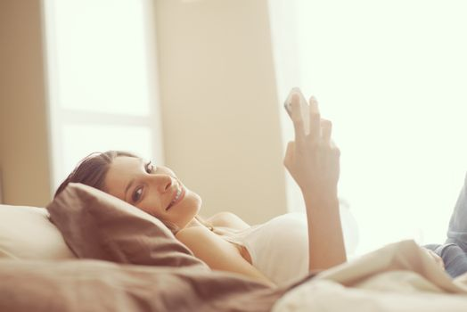 Portrait of a smiling young woman relaxing on her bed texting on her phone