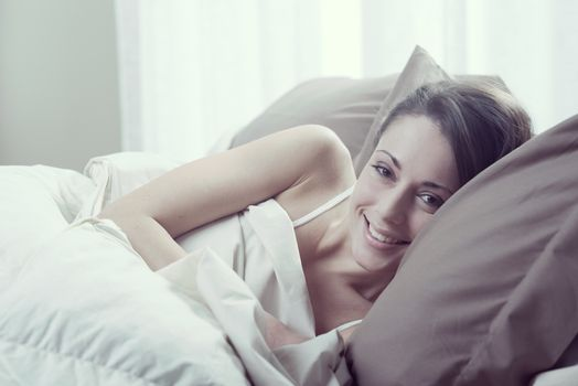 Young woman lying in bed and smiling at the camera