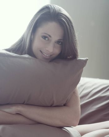 Young woman embracing her pillow in the morning
