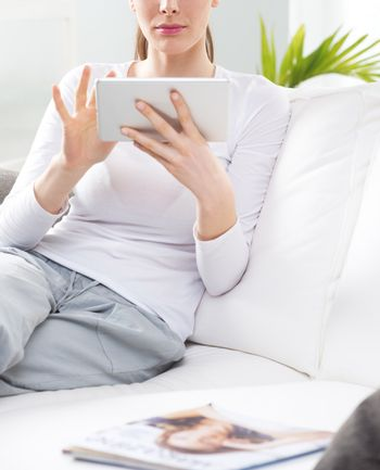 Woman relaxing in the living room using digital tablet.