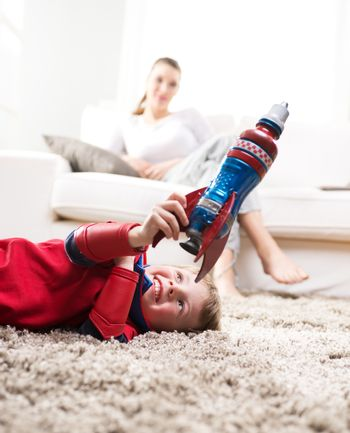 Cute superhero boy paying with toy rocket in the living room with his mother on background.