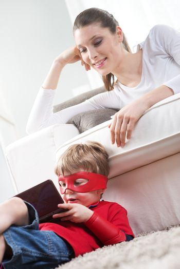 Cute superhero boy playing videogames sitting on carpet with his mother on background.