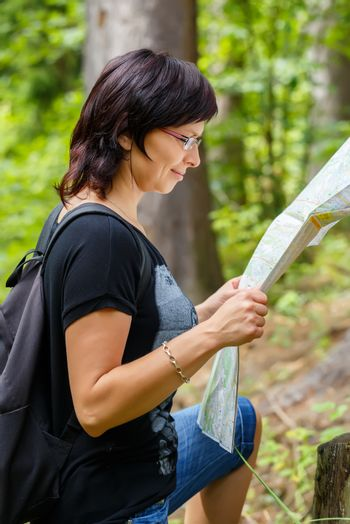 Woman sightseeing outdoors and holding a map in forrest