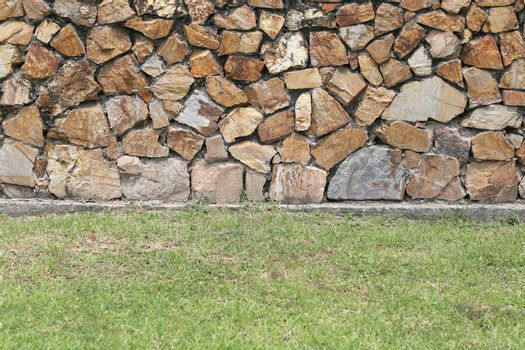 Brown stone wall and green lawn for background.