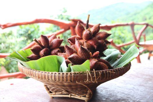 Fresh Salak snake fruit in basket on the foods table.