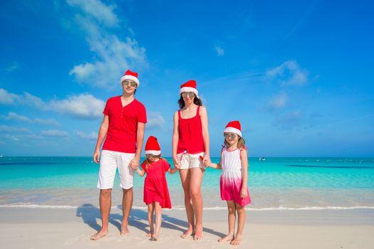Family of four in Santa Hats having fun on tropical beach