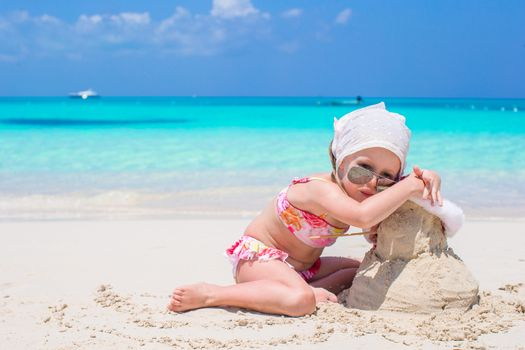 Adorable little girl on seashore with snowman