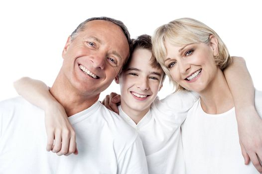 Happy smiling couple with their son posing at studio