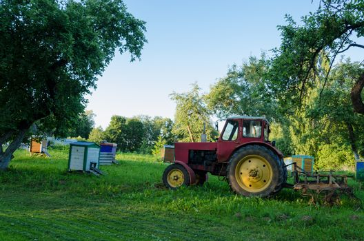 rural farm tractors in the summer garden to the hive